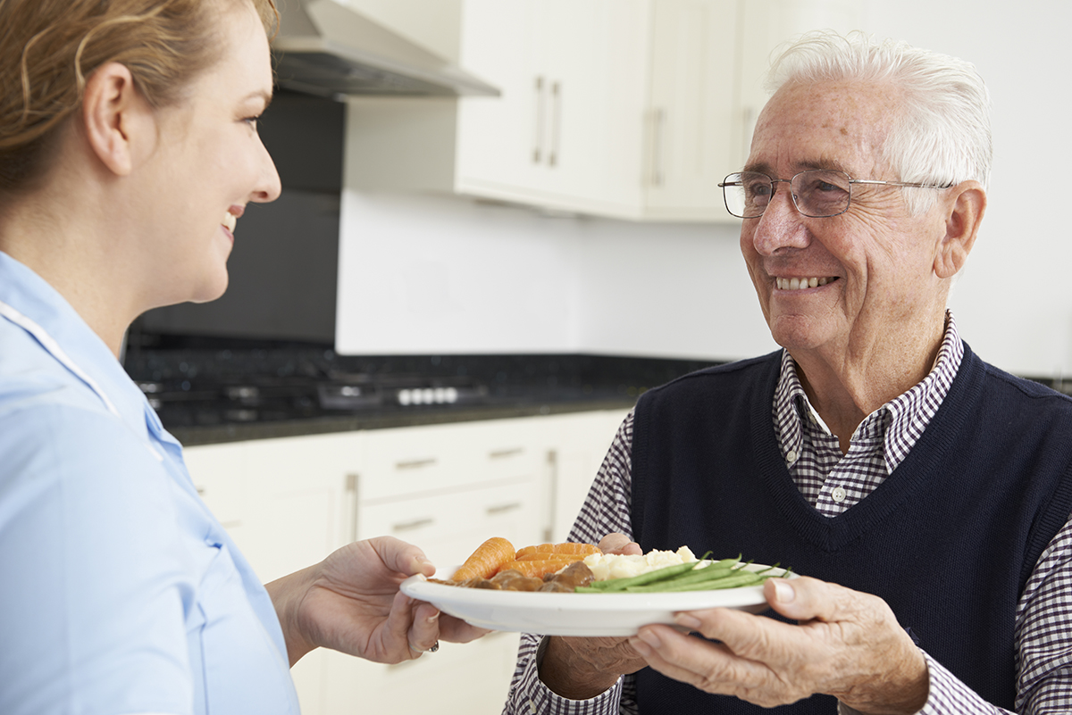 caregiver serving lunch to senior male