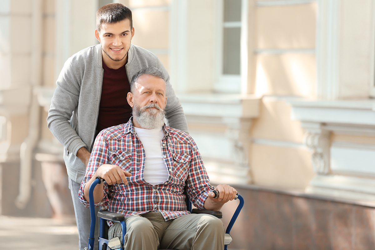 male caregiver pushing senior male in wheelchair