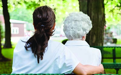 image of caregiver sitting on park bench with senior