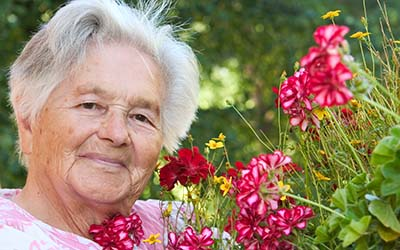 image of senior with flowers outside