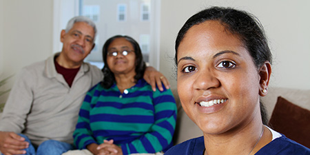 Caregiver in front senior couple that needs assistance