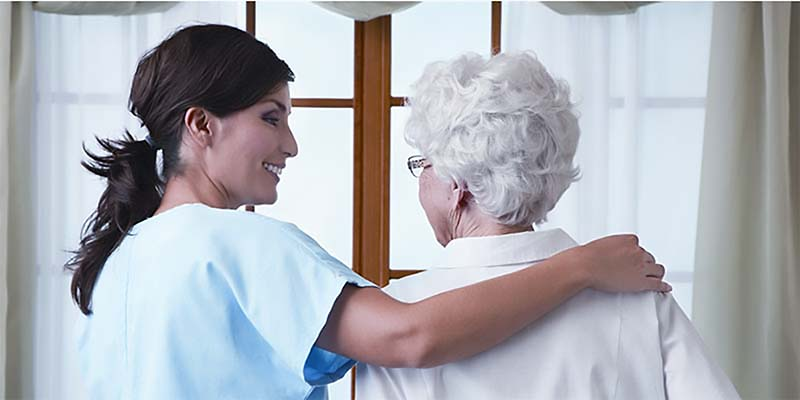 image of caregiver offering support for senior